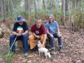 Rinpoche in the forest with retreatants and dog